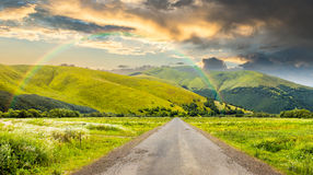 Abandoned road through meadows in mountain. Composite landscape with abandoned asphalt road rolls through meadows with flowers going to high  mountains with Stock Image