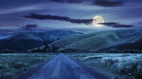 Abandoned road through meadows in mountain at night. Composite landscape with abandoned asphalt road rolls through meadows with flowers going to high  mountains Royalty Free Stock Photos