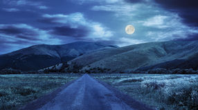 Abandoned road through meadows in mountain at night. Composite landscape with abandoned asphalt road rolls through meadows with flowers going to high  mountains Royalty Free Stock Photography