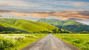 Abandoned road through meadows in mountain at sunrise. Composite landscape with abandoned asphalt road rolls through meadows with flowers going to high Royalty Free Stock Image