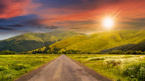 Abandoned road through meadows in mountain at sunset. Composite landscape with abandoned asphalt road rolls through meadows with flowers going to high  mountains Stock Photo