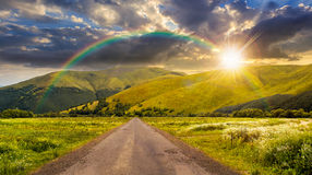 Abandoned road through meadows in mountain at sunset Royalty Free Stock Photos