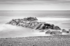 Abandoned Rock Pier. Fine art black and white image of a rocky jetty pier, abandoned in the morning smooth sea waves royalty free stock image