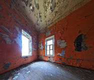 Abandoned room interior. Abandoned interior with two windows in corner. Orange wall color. Wide angle shot Stock Photo