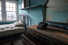 Abandoned Room with an old phone and dresser. Abandoned bedroom in Adler Hotel, New York Royalty Free Stock Photo