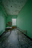 Abandoned room in an old psychiatric asylum. Old patient room in an abandoned asylum Stock Photography