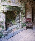 Abandoned Room Trematon Castle. Old abandoned room in the Norman Keep of Trenton Castle Cornwall. Old stone fireplace covered in moss, there is an old chair Royalty Free Stock Photography