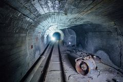 Abandoned round underground mine tunnel with remnant of equipment, pipeline and narrow-gauge railway Royalty Free Stock Image