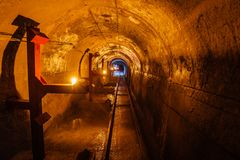 Abandoned round underground technical mine tunnel with a narrow-gauge railway.  Royalty Free Stock Photography