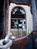 Abandoned ruins. A broken window viewed through an hole in a locked door Royalty Free Stock Image