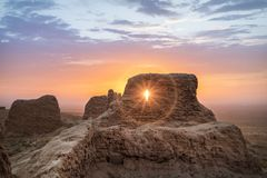 Abandoned ruins of Ayaz Kala fortress, Uzbekistan. Rays of rising sun permeate through ruins of ancient Ayaz Kala fortress in Kyzylkum desert, Uzbekistan royalty free stock photos
