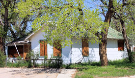 Abandoned Rundown Home. Boarded up white house on a tree lined street stock photos