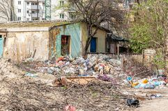 Abandoned rural damaged house in the ghetto near new residential building in the city used as garbage dump with junk and litter in. The yard polluting the stock photography