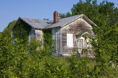 Abandoned Rural One Room Schoolhouse. An abandoned one-room rural school house located in Kansas, United States.  It is almost hidden among the trailing vines Royalty Free Stock Image