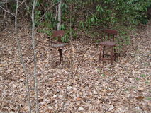 Abandoned rusted chairs in forest. Two old rusted chairs sitting abandoned in a forested Appalachian setting Stock Image