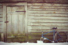 Abandoned rustic look. With an old door and a broken bicycle. Vintage toming Stock Image