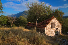 Abandoned rustic stone house. In Dalmatia and coastal mountain range Biokovo behind Royalty Free Stock Photography