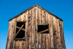 Abandoned rustic wood shack under blue sky in a ghost town royalty free stock image