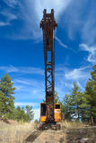 Abandoned Rusting Antique Orange and Black Crane with Blue Sky at a Low Angle Royalty Free Stock Image