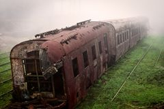 Abandoned rusting train and empty train tracks photographed in a foggy day Royalty Free Stock Images
