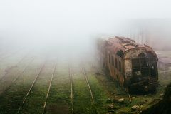 Abandoned rusting train and empty train tracks photographed in a foggy day Stock Image