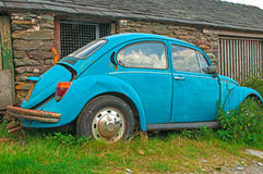 Abandoned Rusting Volkswagon Beetle by Farm Building Royalty Free Stock Images