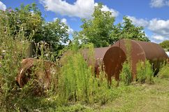 Abandoned rusty barrels and tanks in the weeds Stock Photo