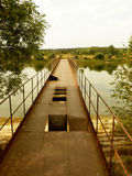 Abandoned rusty bridge over the lake. In the village Royalty Free Stock Photos