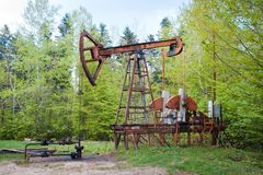 Abandoned rusty broken oil pump and pipeline equipment in forest, oil extraction rig stock images