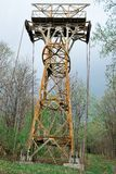 Abandoned rusty cable-way pillar in forest stock images