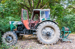 An abandoned rusty and camouflage vintage tractor Royalty Free Stock Photo
