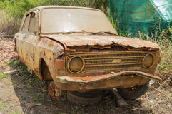 Abandoned rusty car. Abandoned rusty damaged car with wheels disassembled is parked neer the garage stock photos