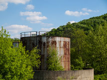 Abandoned rusty metal silo with concrete wall Stock Photos