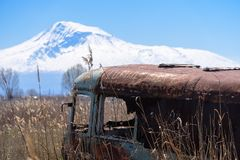 Abandoned and rusty old Soviet Russian bus in the middle of reeds and agriculture fields with Mt. Ararat on the background stock image