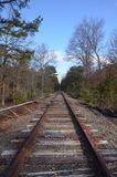 Abandoned Railroad Tracks. Abandoned rusty railroad tracks leading away into the woods royalty free stock image