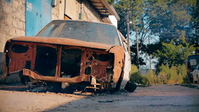 Abandoned rusty red car in the yard in the summer stock video footage