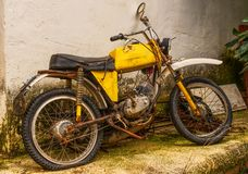 Abandoned, rusty yellow moped. An old yellow moped, circa 1970s, left to rust against an old farm building Royalty Free Stock Images