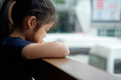 Abandoned Sad and Lonely Asian Child. Sits next to window Royalty Free Stock Photos
