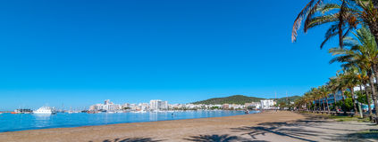 Abandoned sailboat on Ibiza waterfront.  People walking on beach in the distance.  Man paddles his board toward beach.  Royalty Free Stock Images