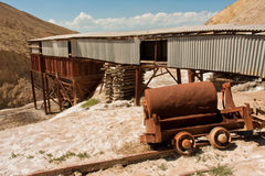Abandoned salt mine and the rails in mountains of Central Asia under bright sun. KYRGYZSTAN, CENTRAL ASIA: Abandoned salt mine and the rails in mountains of Royalty Free Stock Image