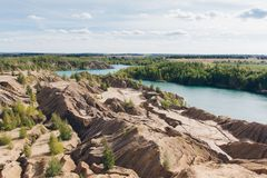 Abandoned sand quarry to the blue lake Royalty Free Stock Photography