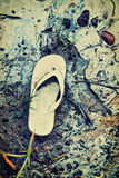 Abandoned Sandal on A Toxic Beach - Retro. An old abandoned child's sandal is left at a beach surrounded by muddy sand contaminated with toxic chemical gasoline Royalty Free Stock Photo