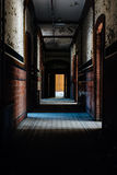 Abandoned School for Boys - Hallway with Tile and Peeling Paint Walls - New York. An dark interior hallway view with tile floors and tile walls in an abandoned Royalty Free Stock Photo