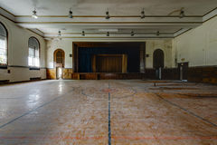 Abandoned School Gymnasium and Stage. An interior view of a derelict gymnasium and stage with a gorgeous hardwood floor at an abandoned school stock photos