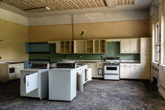 Abandoned School Home Economics Classroom with Washer, Dryer and Stoves. An interior view of a derelict home economics classroom with a washer, dryer and stoves Royalty Free Stock Photos