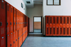 Abandoned School Locker Room with Orange Lockers. An interior view of a derelict locker room near a gymnasium with orange lockers at an abandoned school royalty free stock images