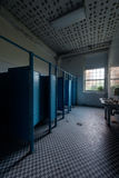 Abandoned School Restroom. An interior view of a derelict blue hued restroom with stalls and sink at an abandoned school Royalty Free Stock Photo