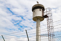Abandoned sentry box tower isolated by a net with barbed wire. Royalty Free Stock Photo