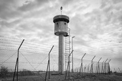 Abandoned sentry box tower isolated by a net with barbed wire. Stock Photo