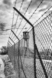 Abandoned sentry box tower isolated by a net with barbed wire. Stock Photography